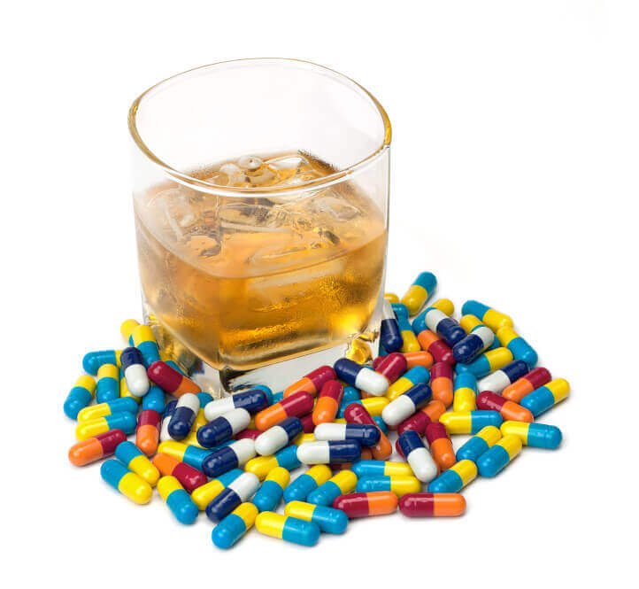 A glass of whiskey surrounded by pills isolated on white.